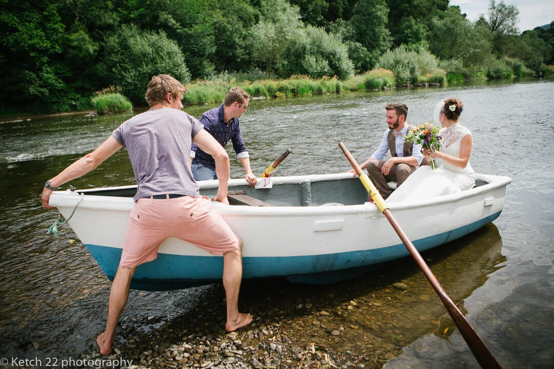 Bride and groom get on rowing boat on river Wye