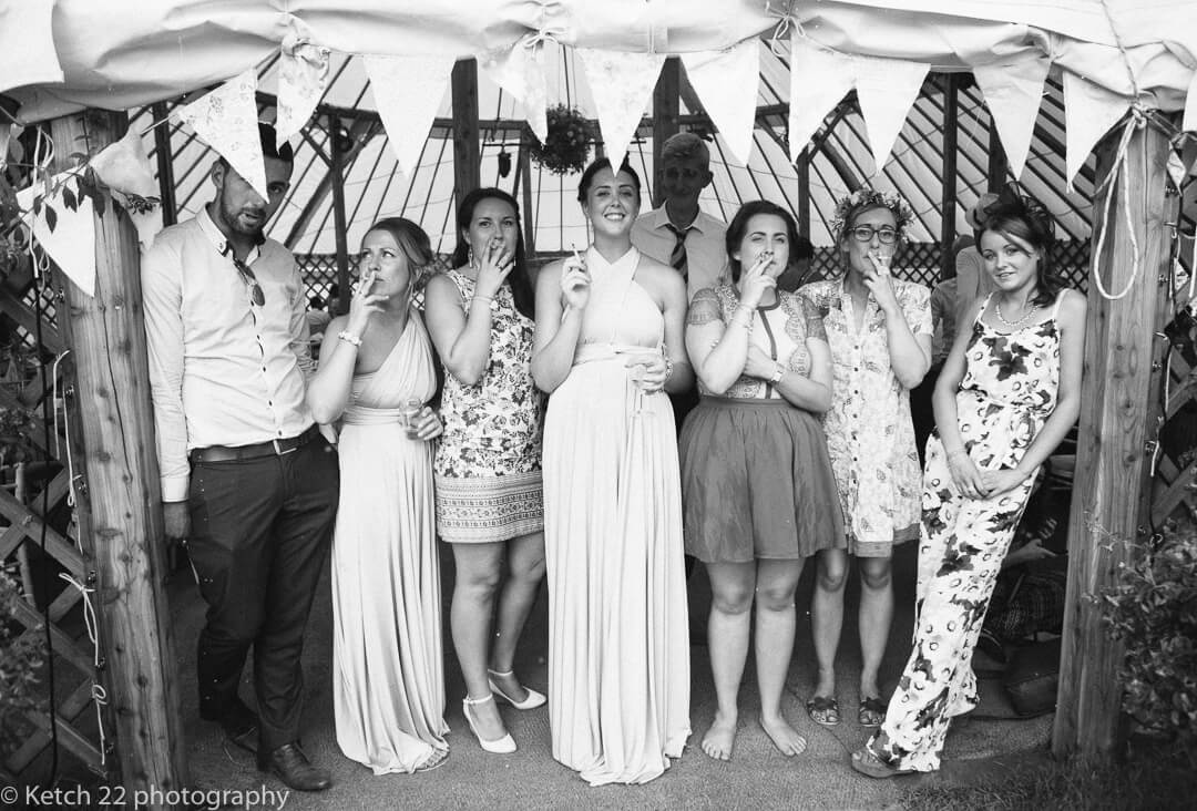 Wedding guests standing in Yurt  and smoking out of the rain