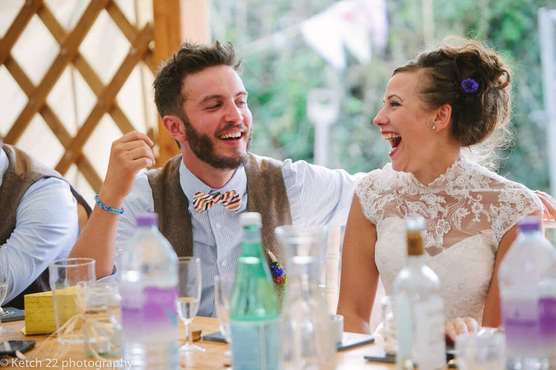 Bride and groom laughing at wedding speeches in Yurt