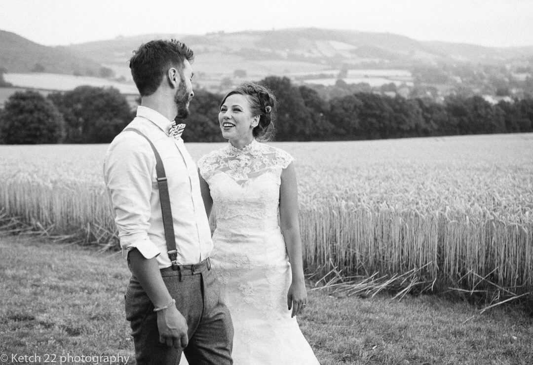 Bride and groom standing in front of wheat feild