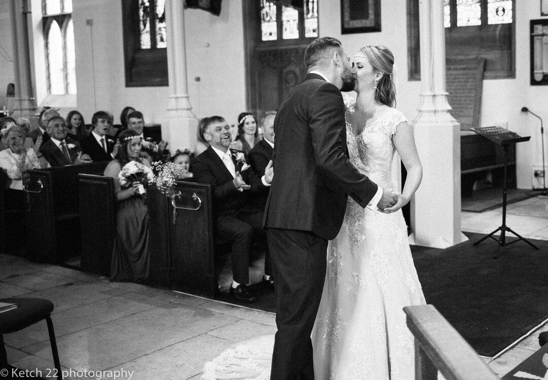 Groom kissing bride at wedding ceremony