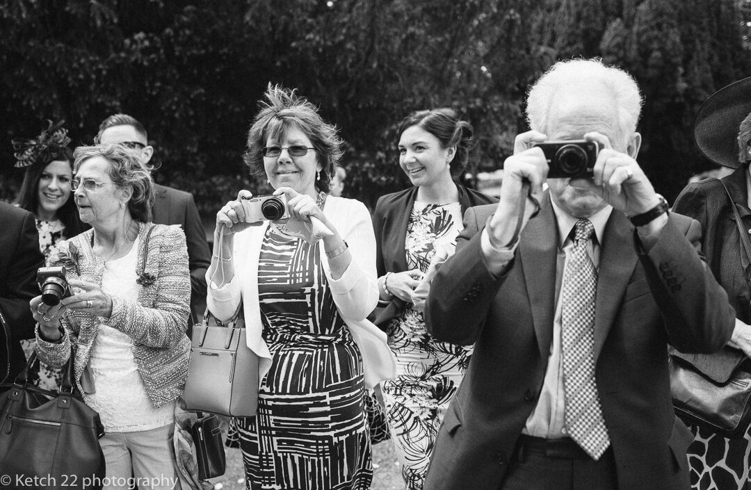 Wedding guests taking photos of bride and groom
