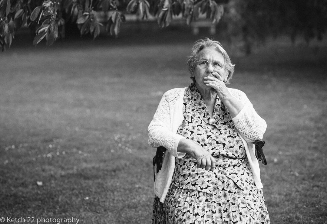 Grandma has a quiet moment alone at garden wedding