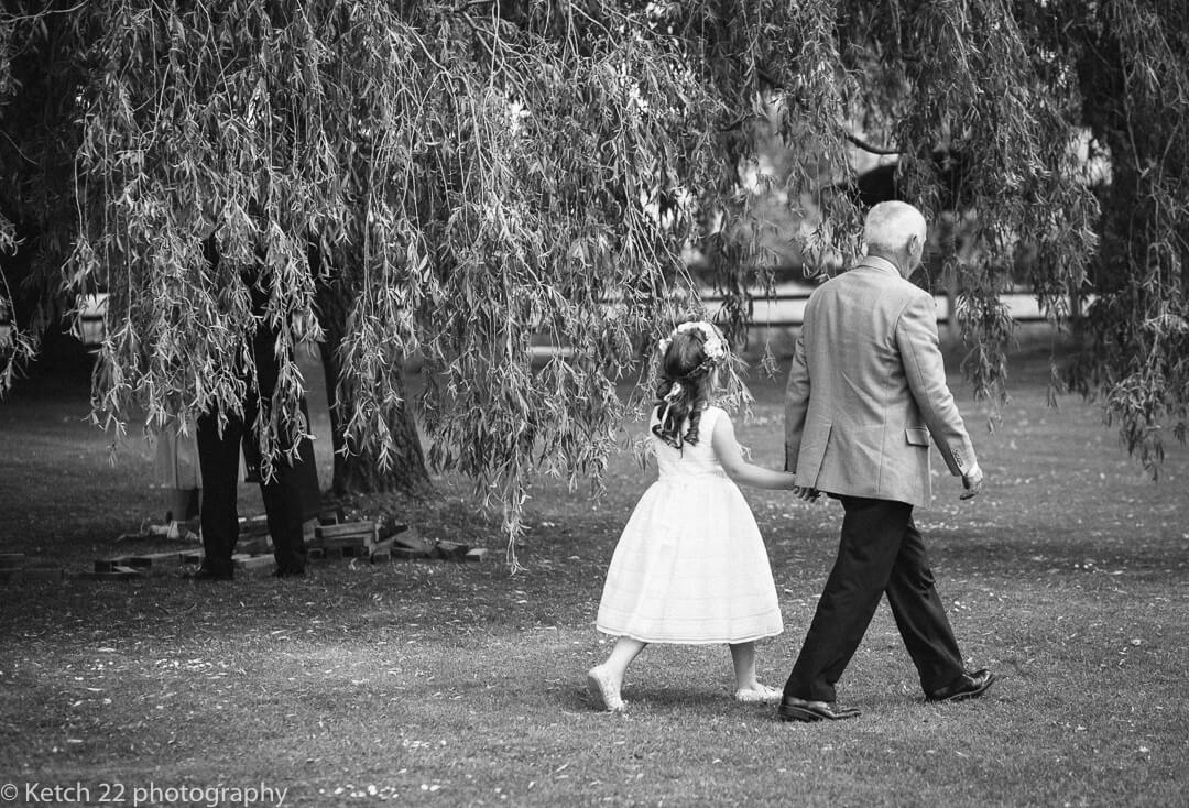 Grandad and flower girl walking through garden at Eastington Park Wedding