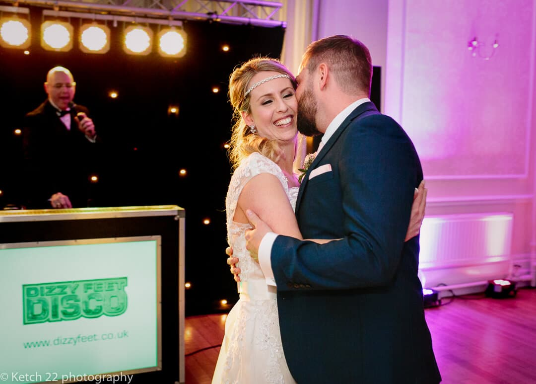 Groom kissing bride during wedding first dance