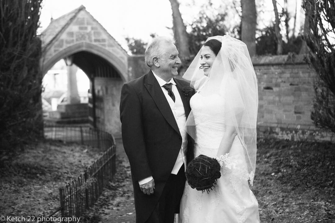Father and bride looking at each other and laughing and smiling just before wedding ceremony
