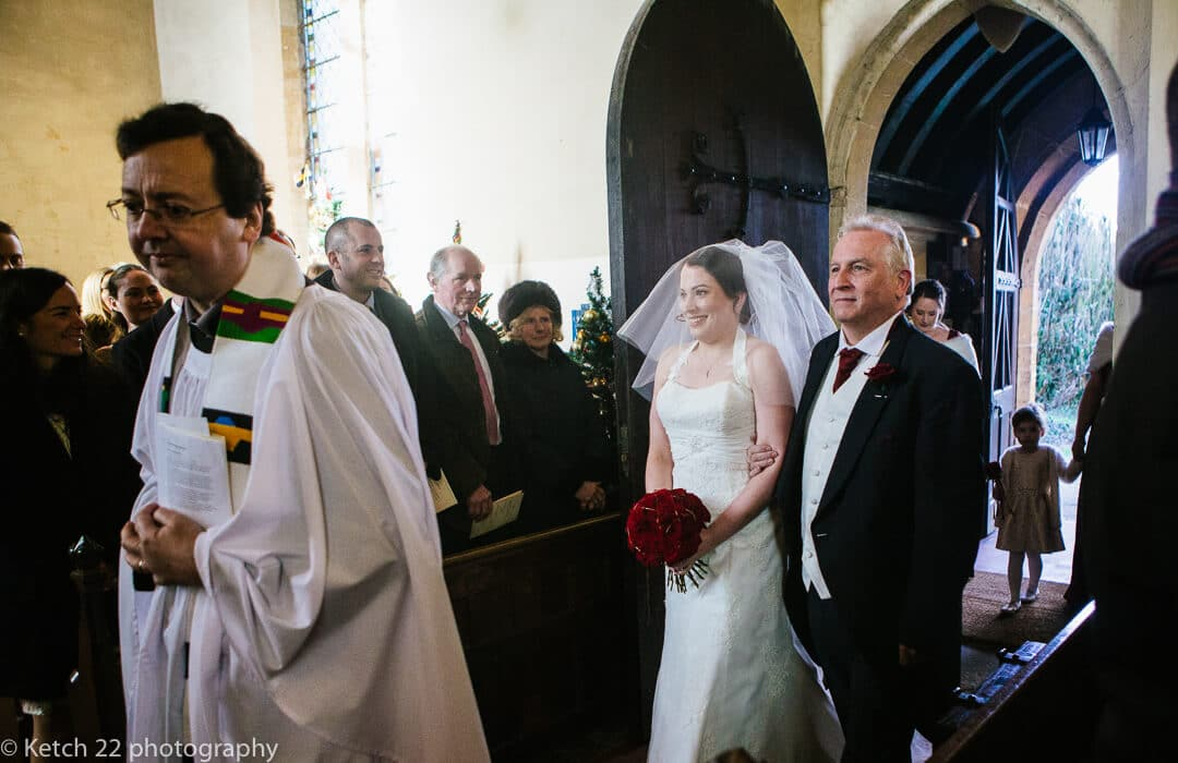 Father and bride entering church with wedding guests looking on
