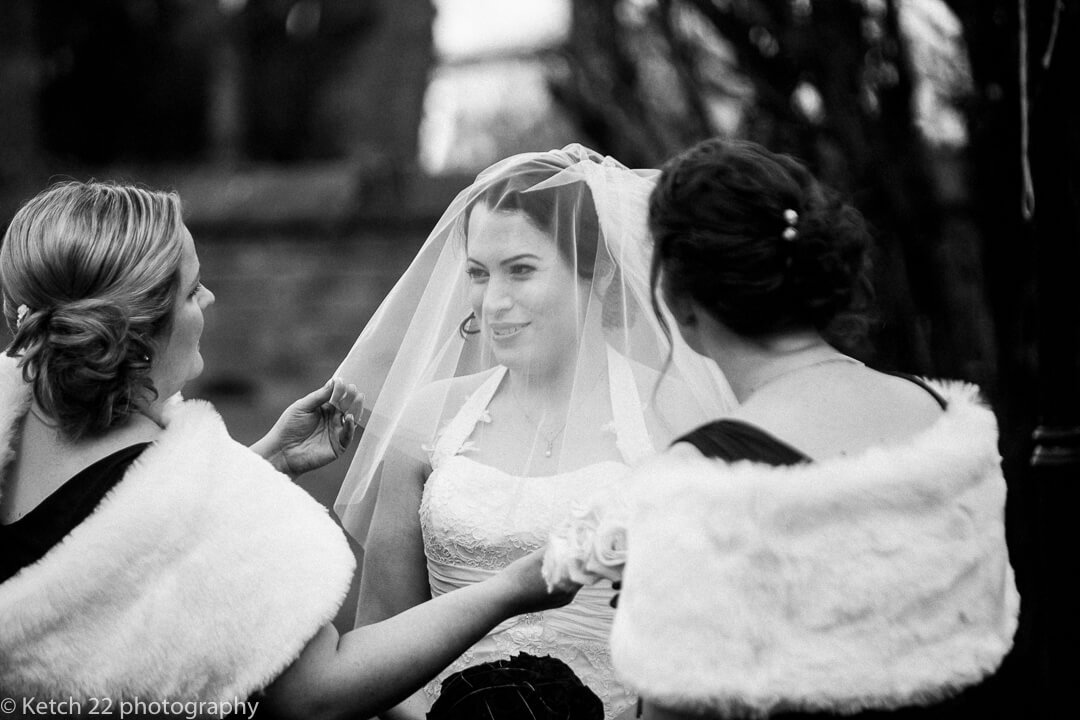 Bridesmaids adjusting brides veil at Winter wedding