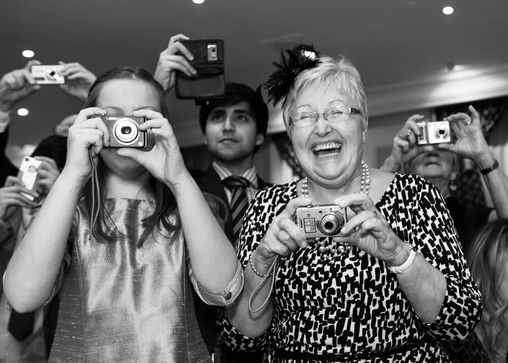 Wedding guests taking photos in Cheltenham Gloucestershire