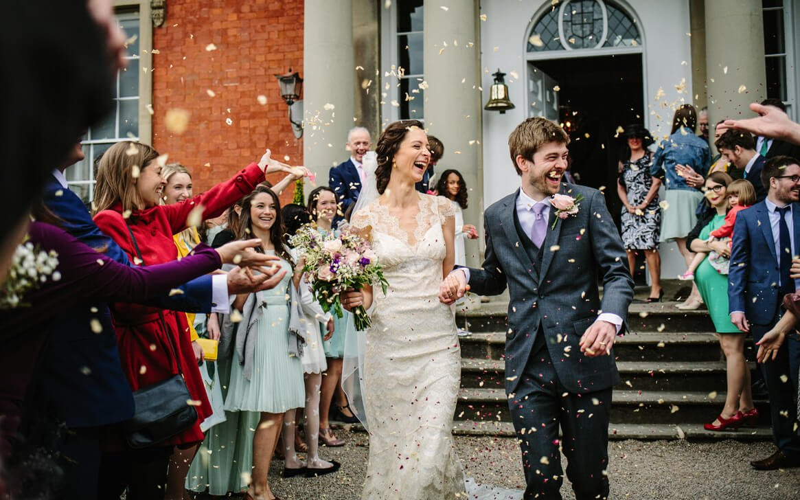 Bride and groom with wedding confetti at Gloucestershire wedding