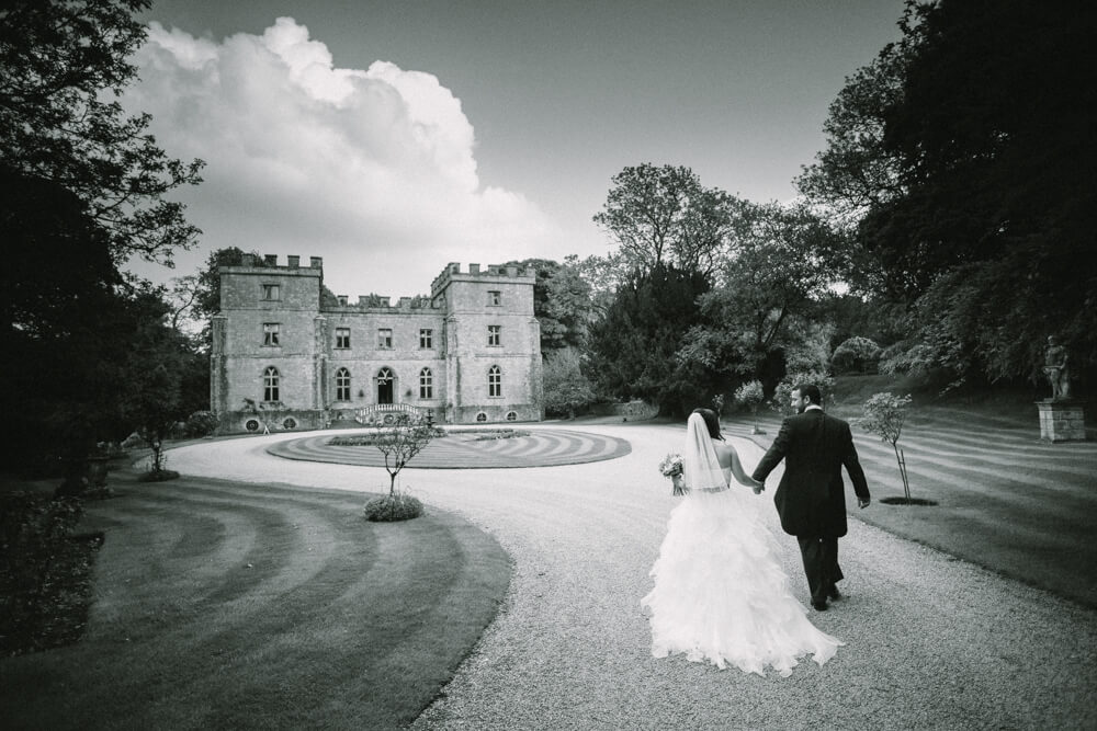 Bride and groom walking in front of Clearwell Castle wedding venue Gloucestershire