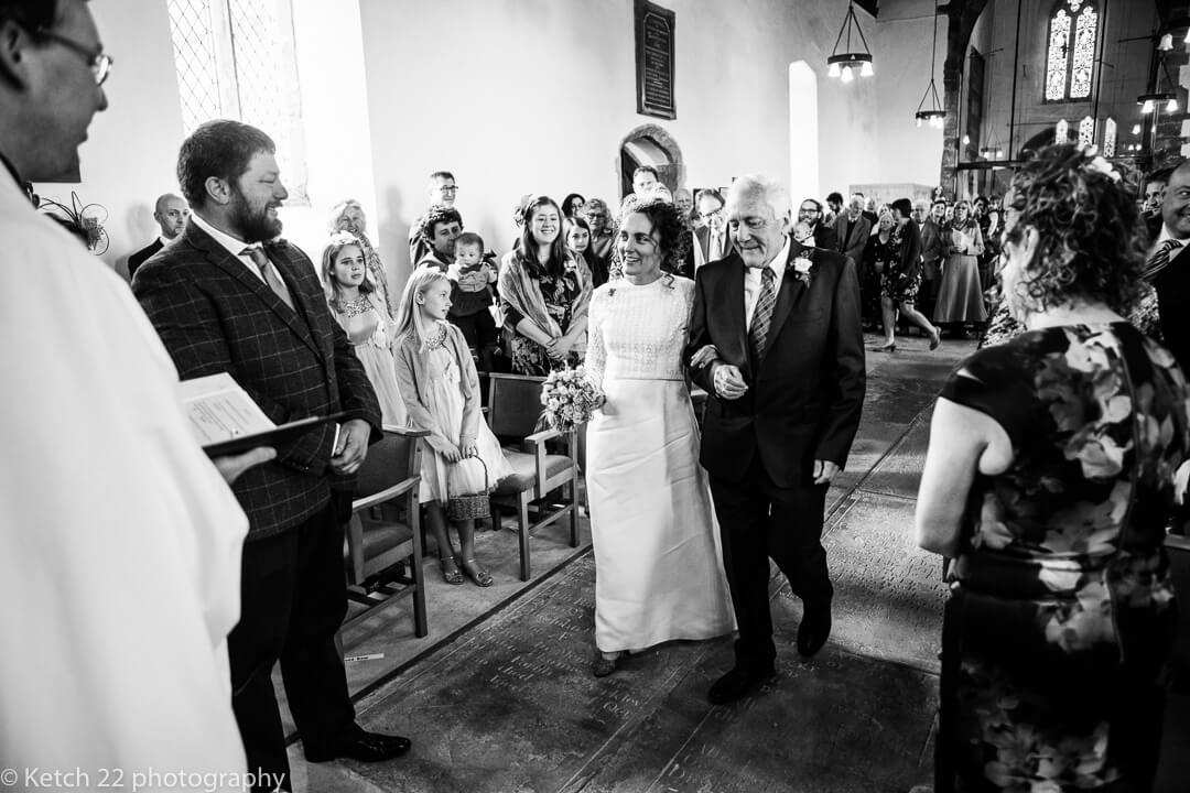 Father and bride walking down church aisle in Gloucestershire