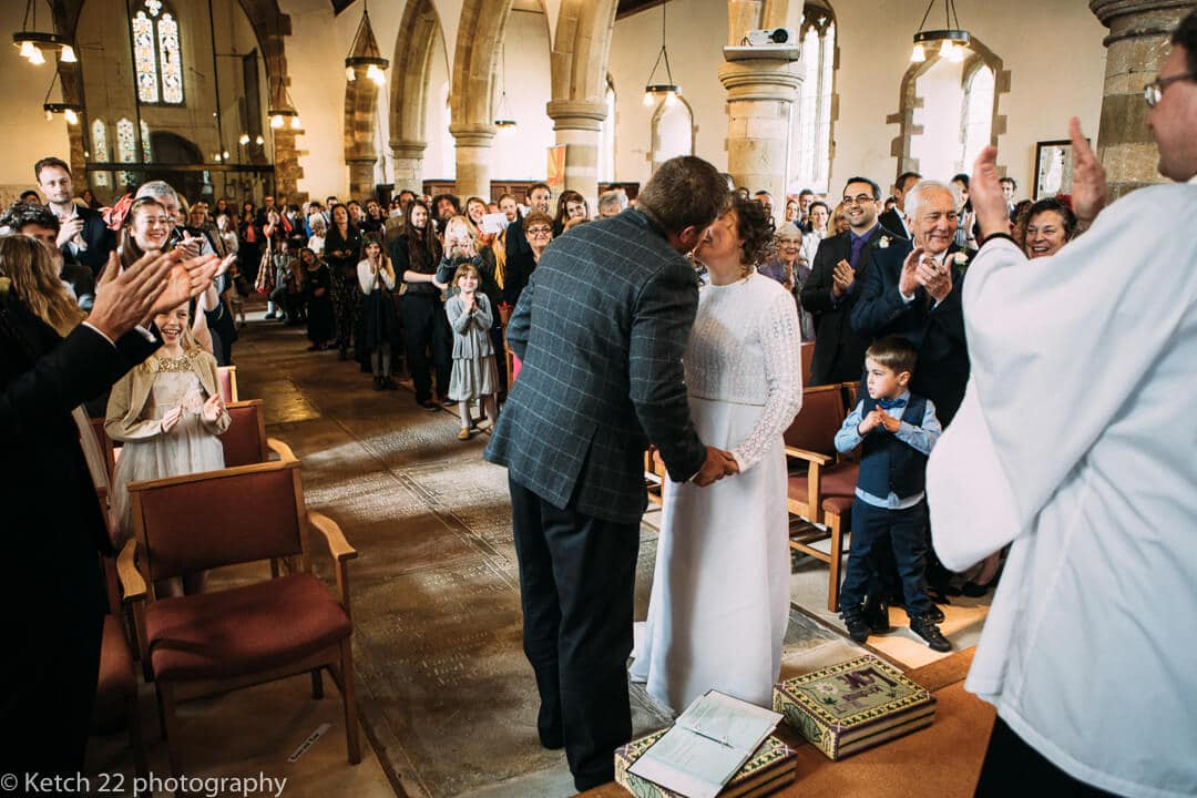 Bride and groom kissing in church wedding ceremony