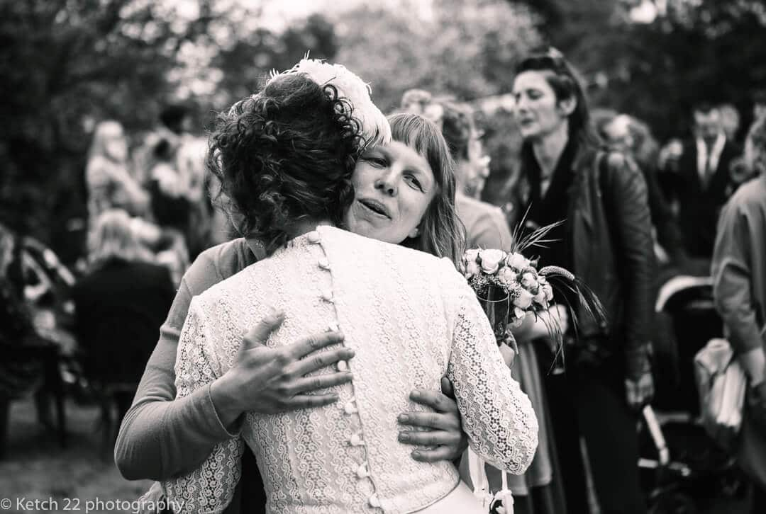 Wedding guest hugging bride