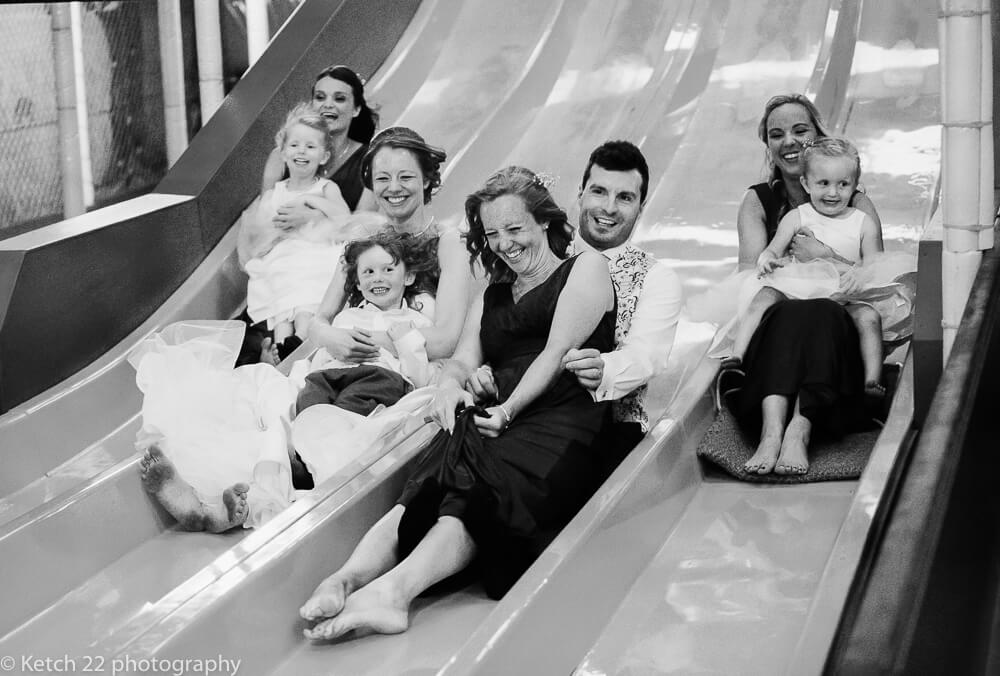 wedding bridal party riding on giant slide at the Wedding at the Barn at Berkeley in Gloucestershire