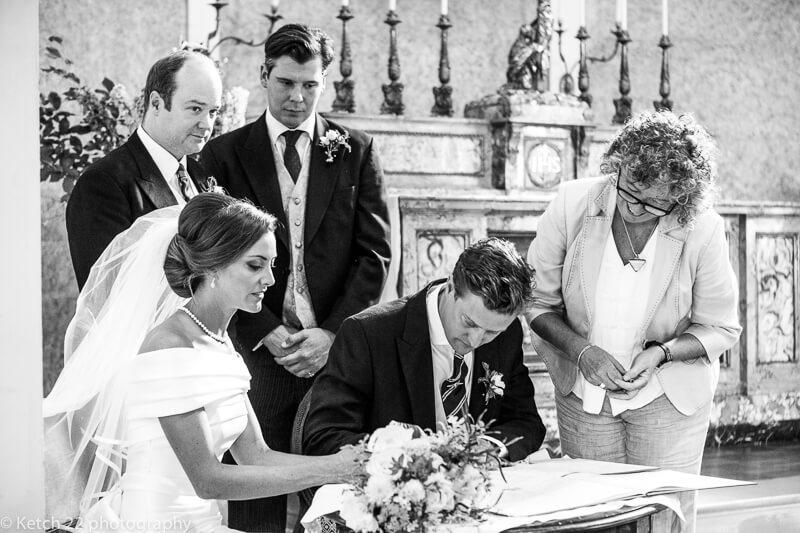 Signing the registrar at Dorset wedding