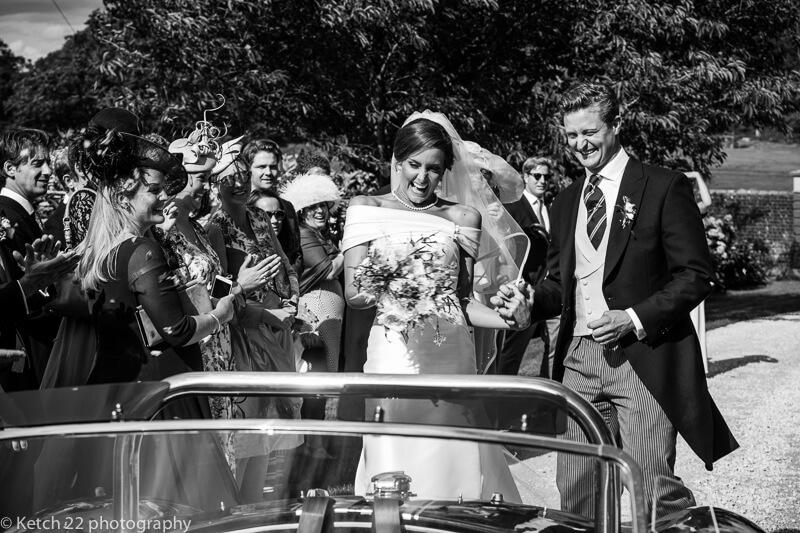 Bride and groom entering sporty wedding car in Dorset
