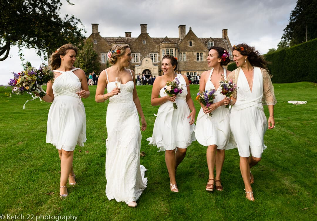 Bride and bridesmaids walking and laughing in front of Hilles House in Gloucestershire
