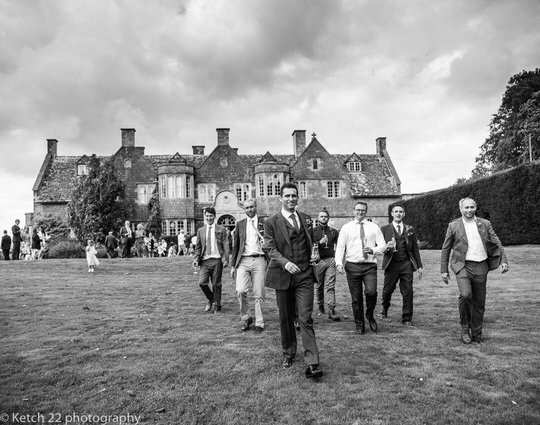 Groom and friends walking in Hilles House gardens