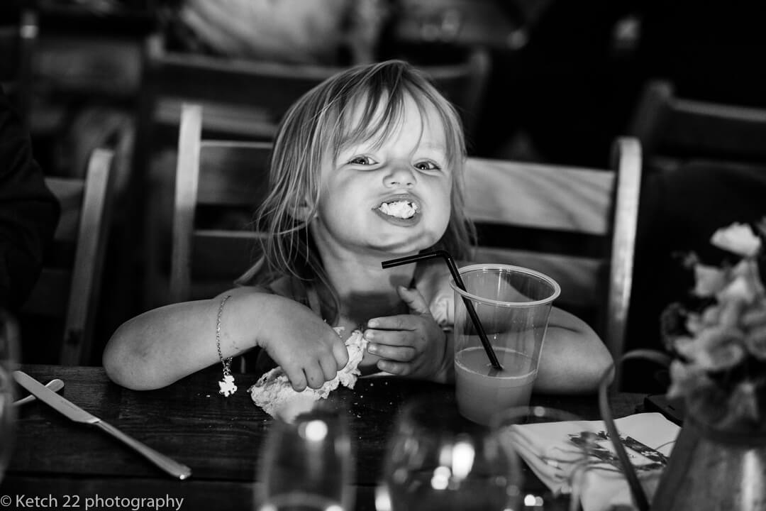 Cheeky little girl with mouth full at weddiing