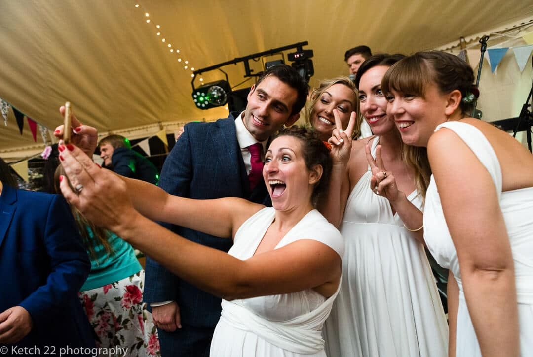 Wedding guests and groom taking selfie at wedding