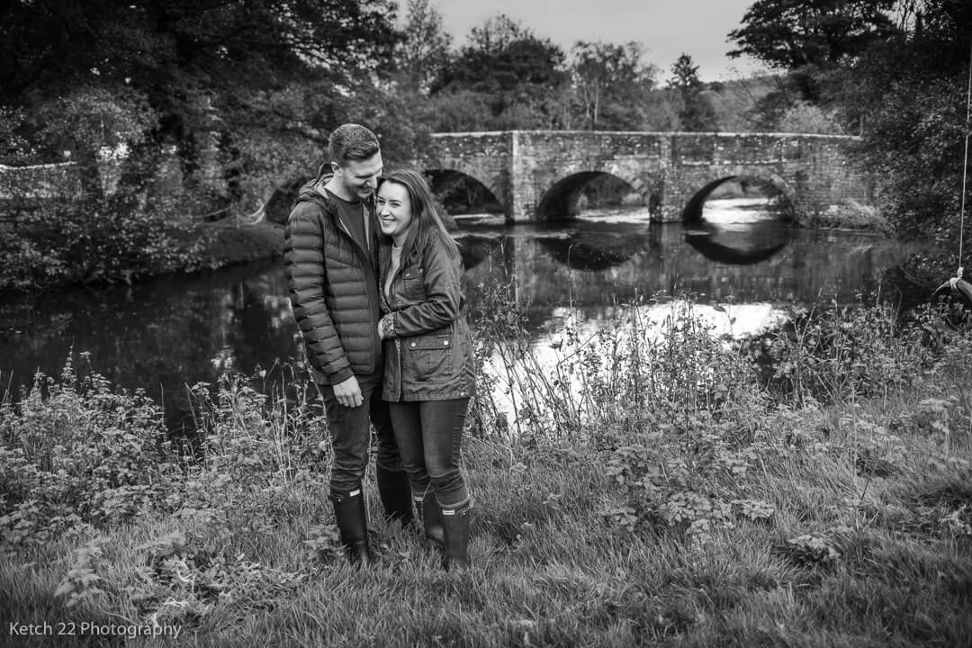 Engaged couple hugging in front of bridge over a river