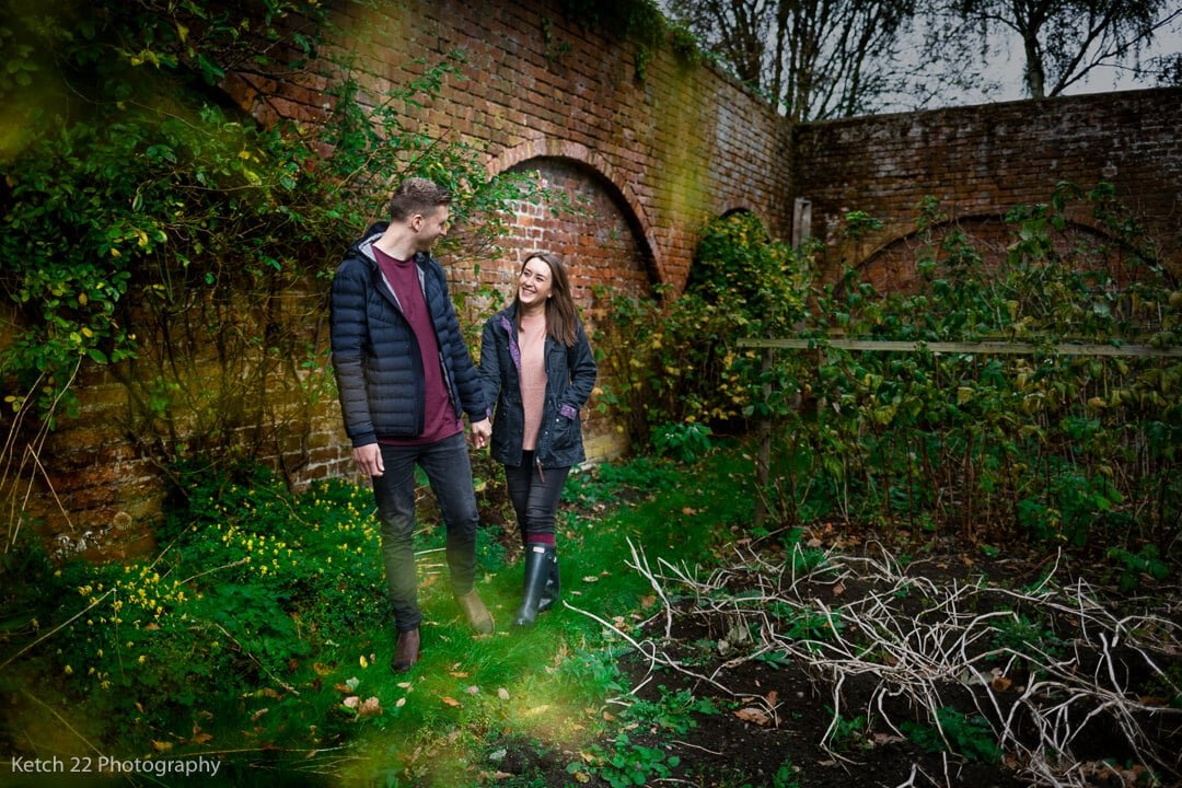 engaged couple walking in walled garden