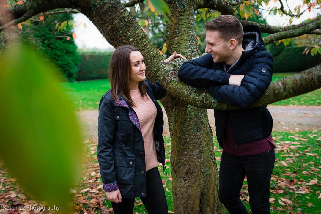 Young couple leaning on tree at rural engagement session Herefordshire