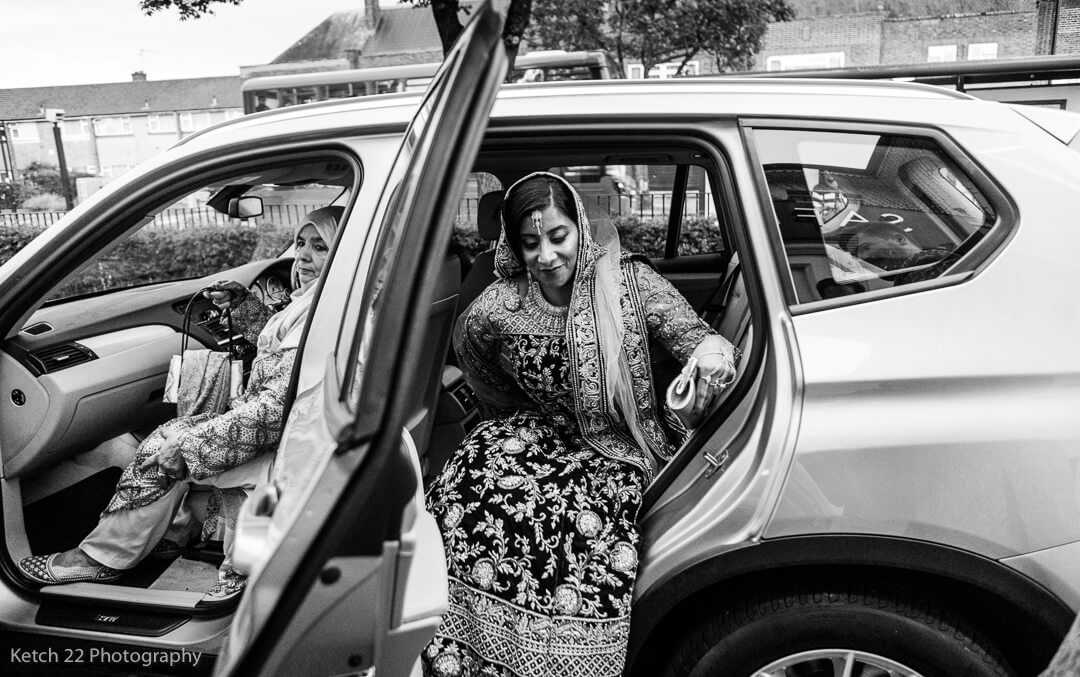 Muslim bride getting out of wedding car in Southall