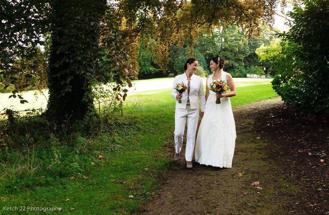 Newly weds walking in garden at Lords of the Manor
