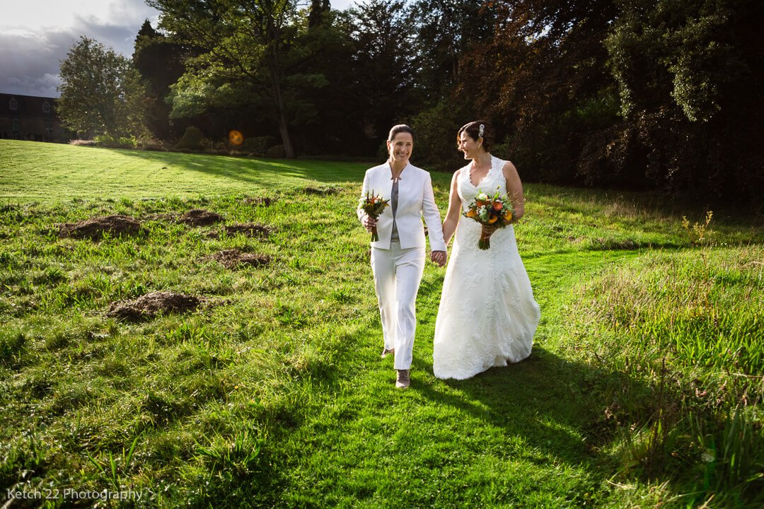 Newly weds walking in garden at Gloucestershire wedding