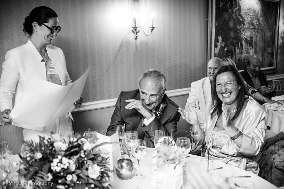 Mother and father of bride laughing during the wedding speeches