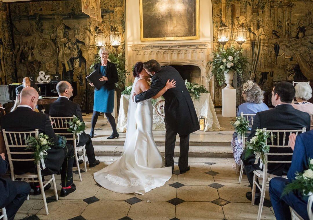 Groom kissing bride just after wedding ceremony in castle