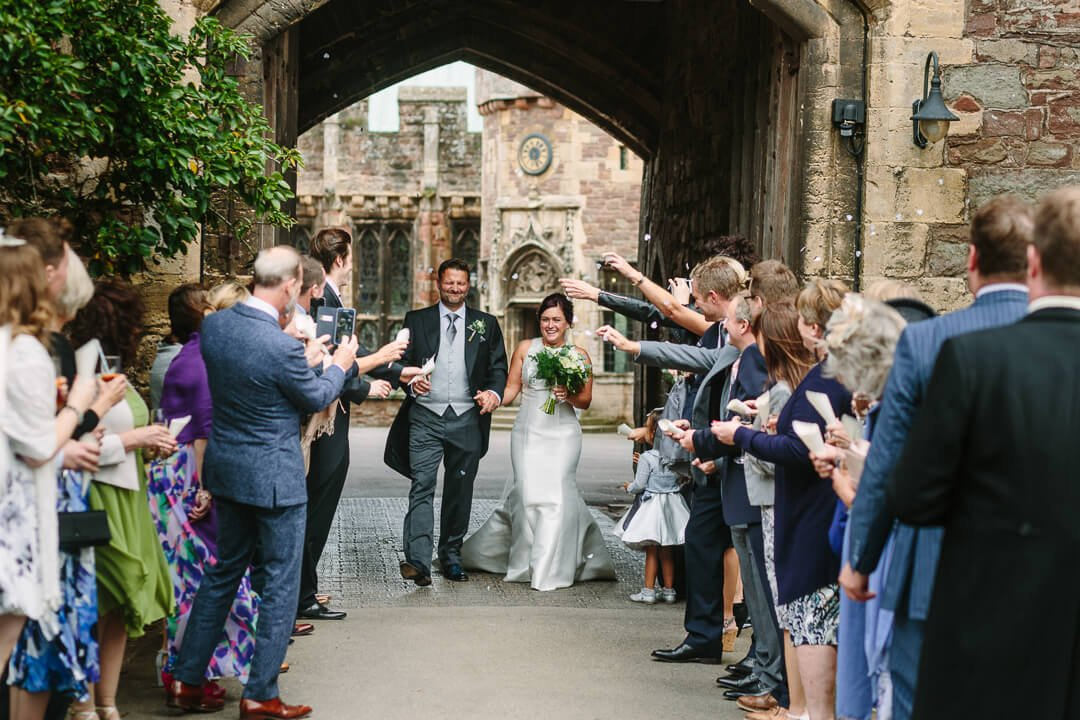 Newly weds getting showered with confetti at Castle wedding