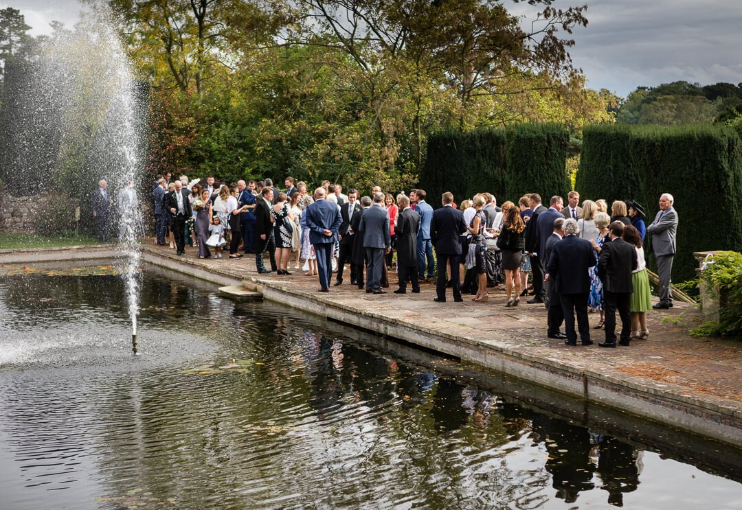 Wedding guests by the fountains at Berkeley castle wedding venue