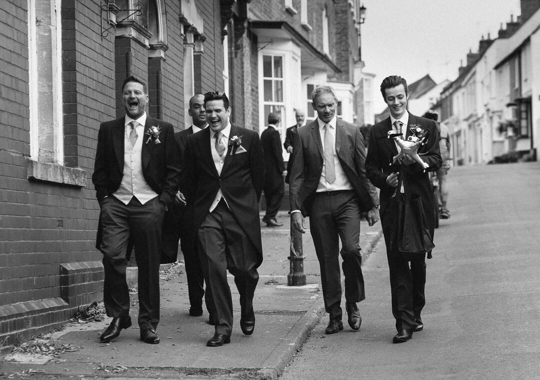 Groom and ushers walking down the street laughing