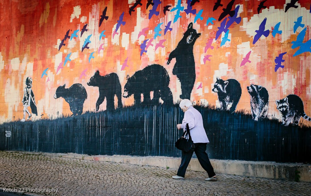 Old lady walking along a street with art mural with bears