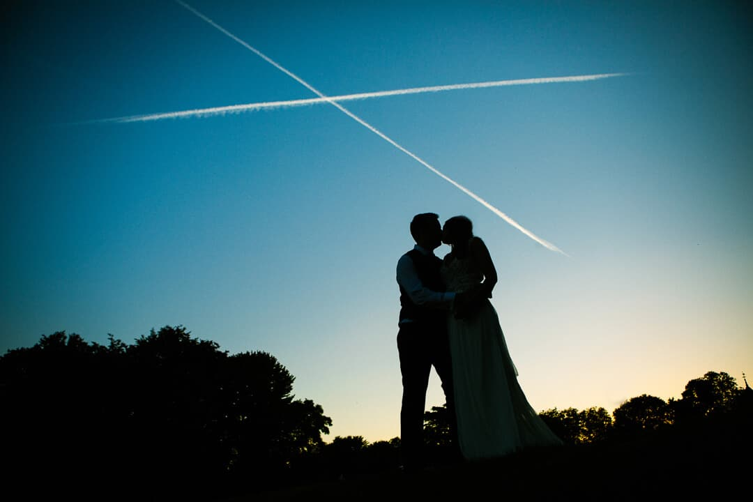 Silhouette of bride and groom kissing at sunset at summer wedding