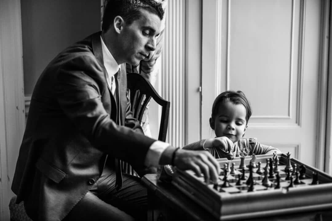 Reportage wedding photograph of child and father playing chess
