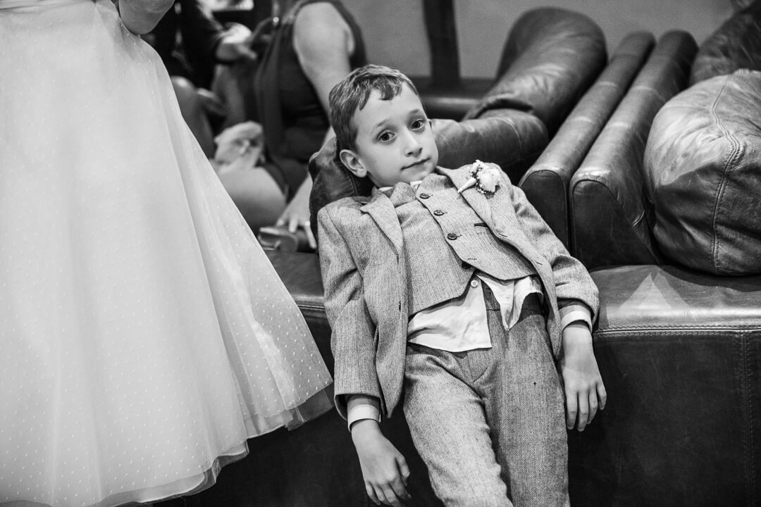 An example of a documentary weddings photo of a bored kid with his shirt hanging out at natural wedding