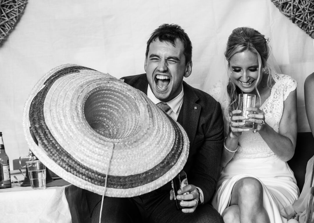 Groom with mexican hat laughing at speeches