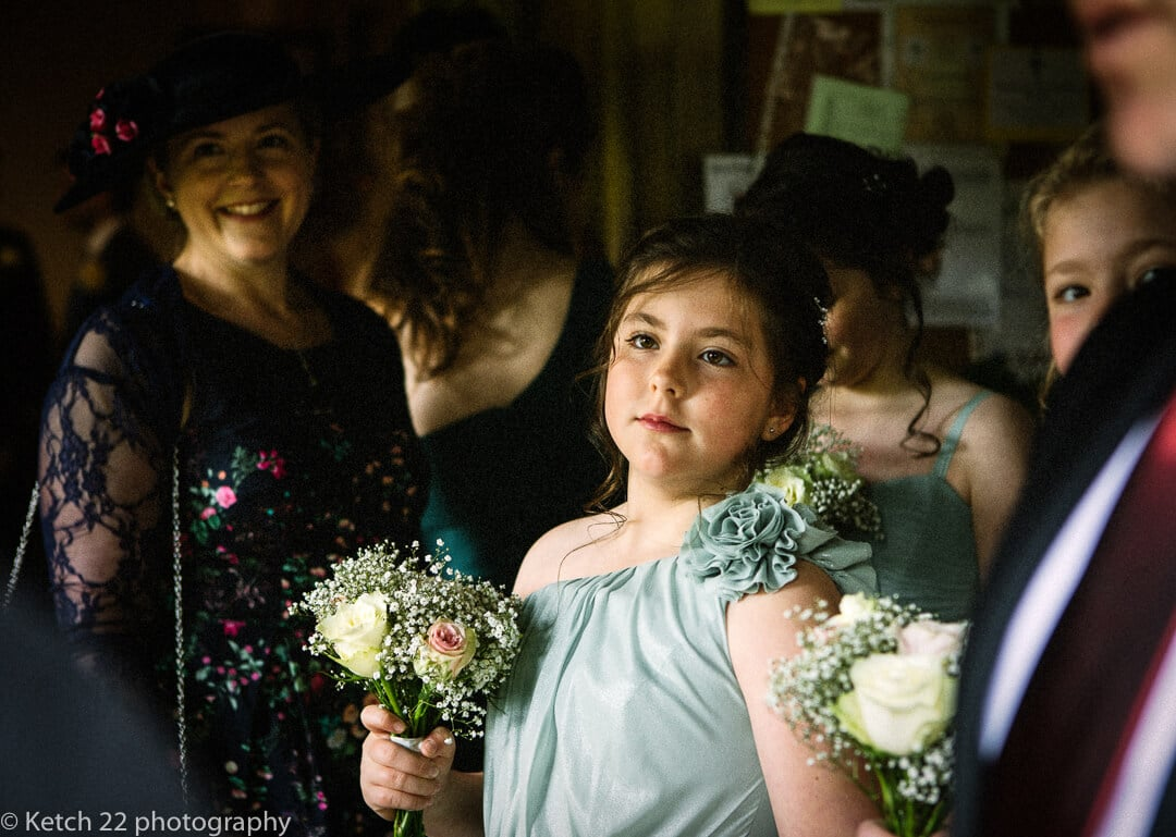 Flower girl waiting in church porch at Oxfordshire wedding
