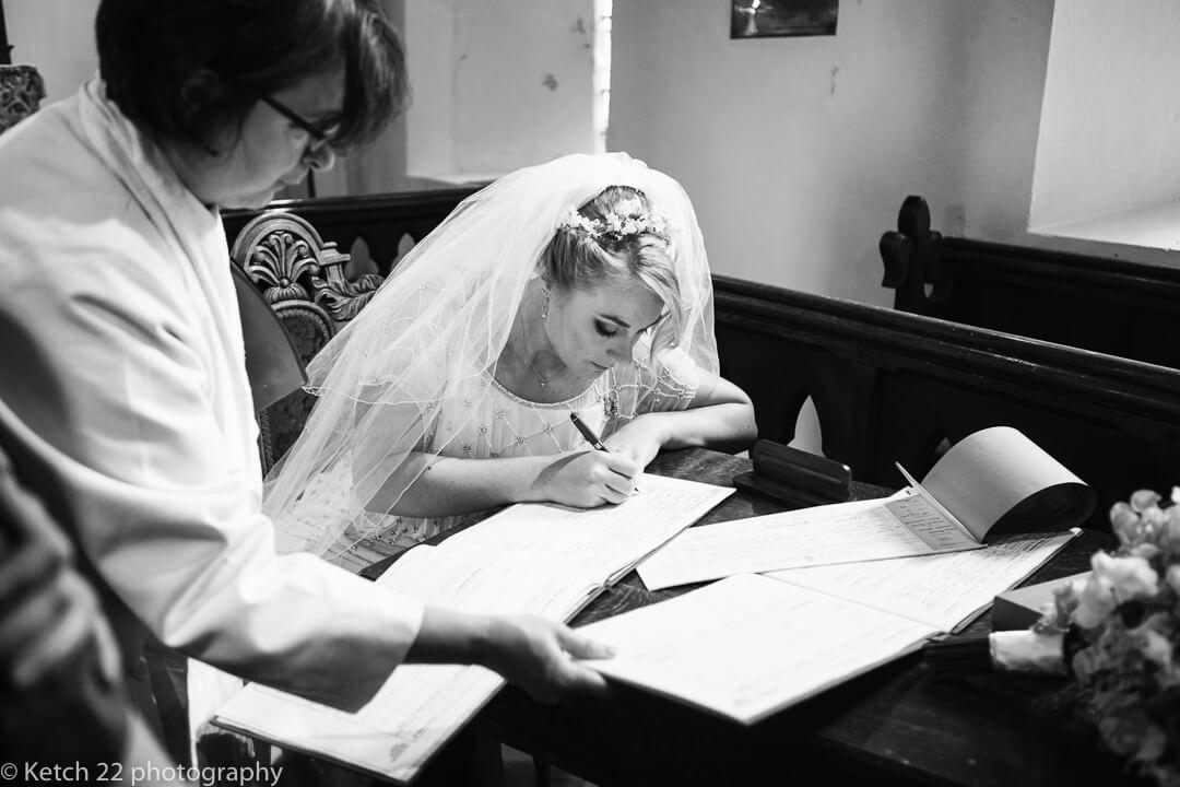 Bride signing registrar at documentary wedding photography Oxfordshire