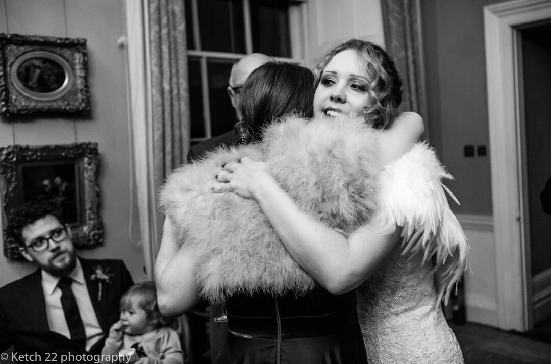 Candid wedding photo of bride hugging guest at North Cadbury Court
