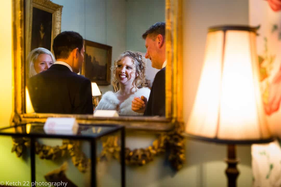 Natural portrait of bride in mirror chatting to wedding guests