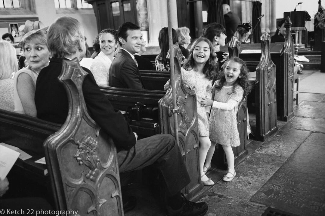 Storytelling wedding photography of flower girls watching the bride enter the church
