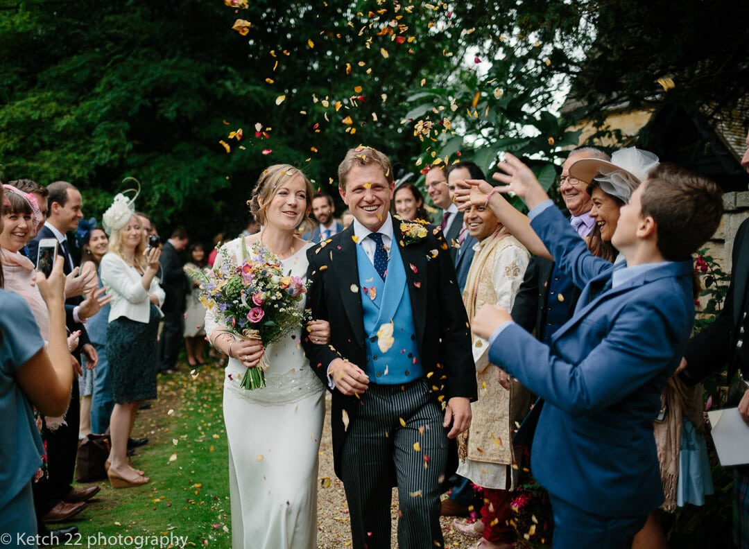 Reportage wedding of bride and groom walking through confetti