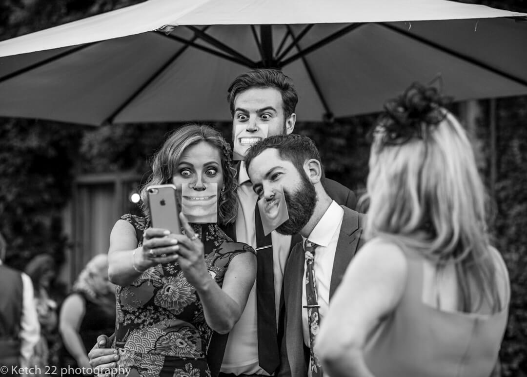 Documentary wedding image of guests fooling around with masks and taking selfies