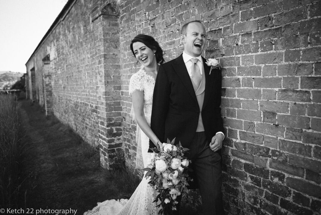 Portrait of bride and groom laughing in garden