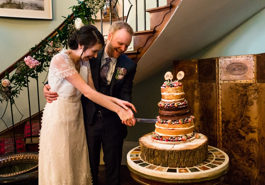 Bride and groom cutting wedding cake at country house
